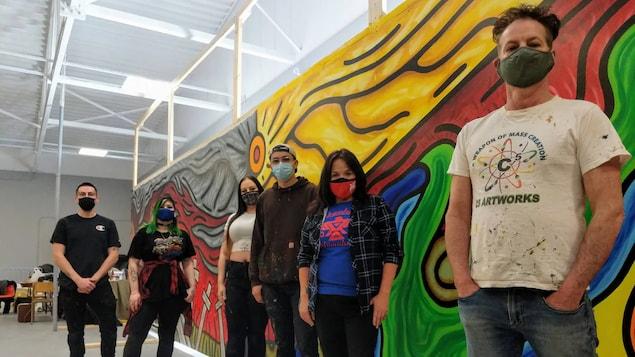 Des gens posent devant une peinture sur un mur.