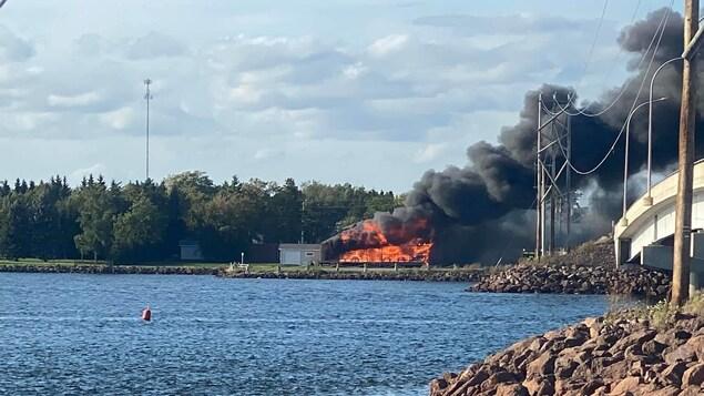 Un restaurant en flamme près d'un cours d'eau et d'un pont.