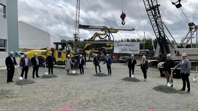 12 personnes tiennent une pelle devant de la machinerie.