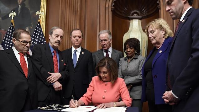 Souriante, Nancy Pelosi signe l'acte d'accusation, entourée des responsables de la mise en accusation et des présidents des comités de la Chambre ayant mené l'enquête en destitution.