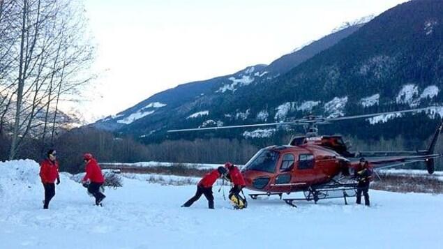 Une équipe de recherche et sauvetage entoure un hélicoptère posé sur une montagne enneigée en Colombie-Britannique.