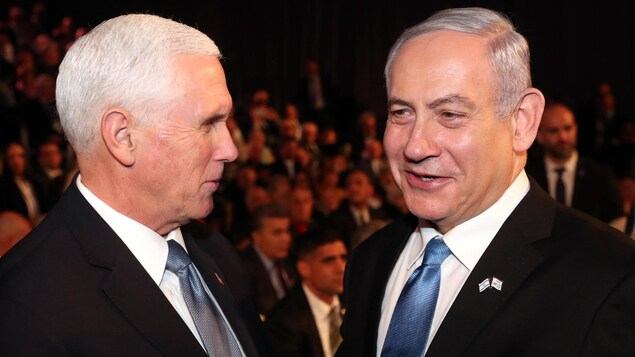 Deux hommes en veston et cravate se souriant devant une assemblée assise.