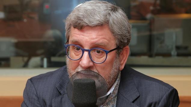 Photo de Régis Labeaume devant un micro de radio.