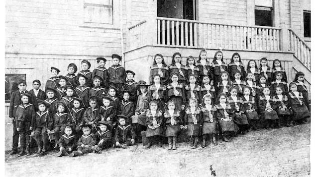 Un groupe d'enfants en uniformes pose devant une école.