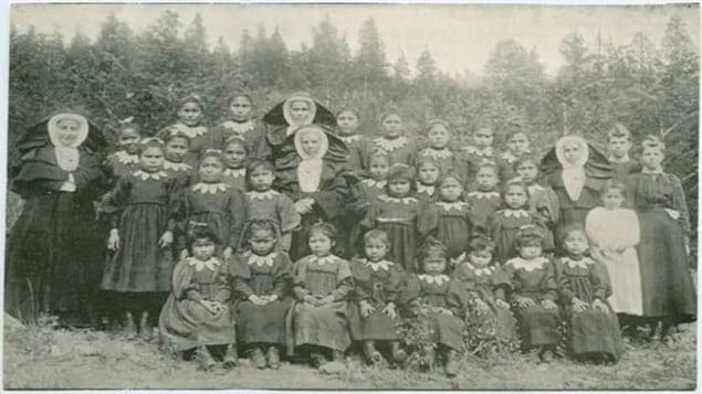 Une photo de classe avec des jeunes filles autochtones entourées de religieuses.