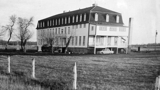 Une vieille photo en noir et blanc montre le bâtiment de trois étages.