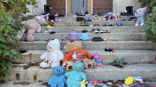Des oursons en peluche et des souliers sur des marches.
