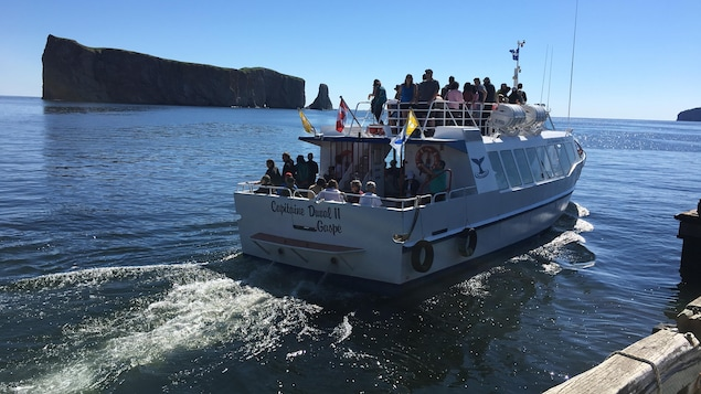 Bateau rempli de touristes devant le Rocher Percé.