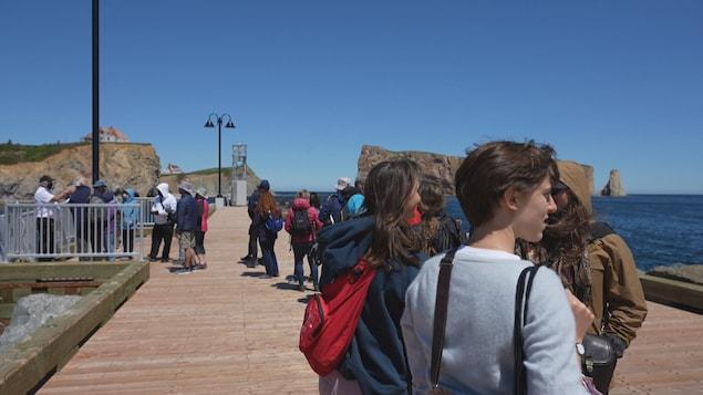 Des touristes admirent la vue sur le Rocher Percé.
