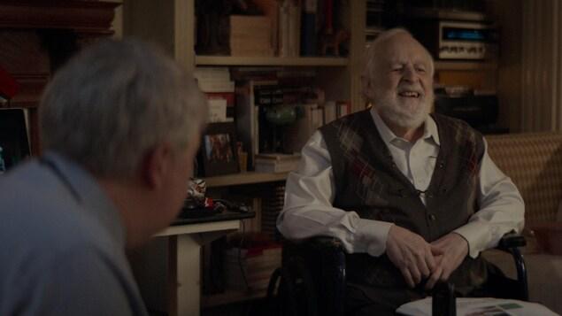 Une scène du court-métrage de Benoit Brière, Mourir en vie, avec Marcel Sabourin. Un vieillard rit dans son fauteuil roulant.