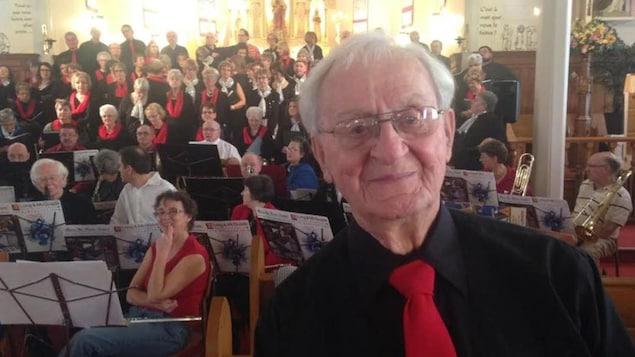 Le père Maurice LeBlanc est devant une chorale.