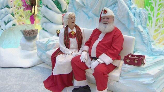 Le père et la mère Noël, assis sur un fauteuil à l'apparence glacée, devant des sapins couverts de neige.