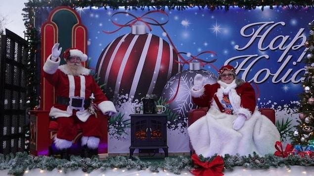 Le père et la mère Noël assis dans leur fauteuil près d'un foyer. Ils envoient la main aux passants.