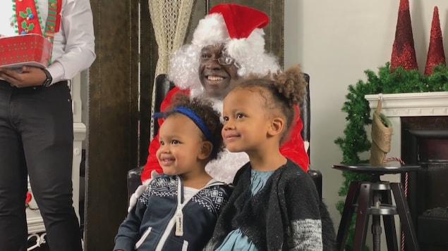 Le père Noël prend la pause avec deux enfants au regard brillant.