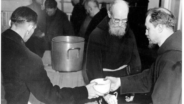 Deux prêtres servent dans une soupe populaire