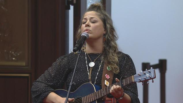 Une femme chante au micro en tenant une guitare.