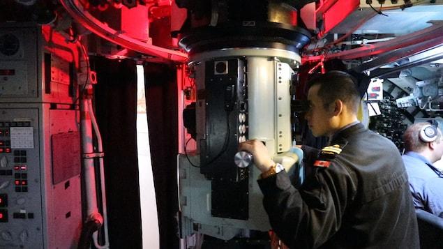 Dans la salle de contrôle, un sous-marinier regarde à travers le périscope