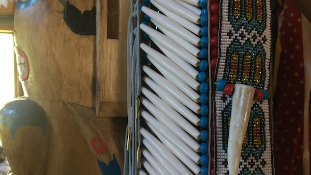 Gros plan sur des perles et une dent qui décorent un habit autochtone traditionnel.