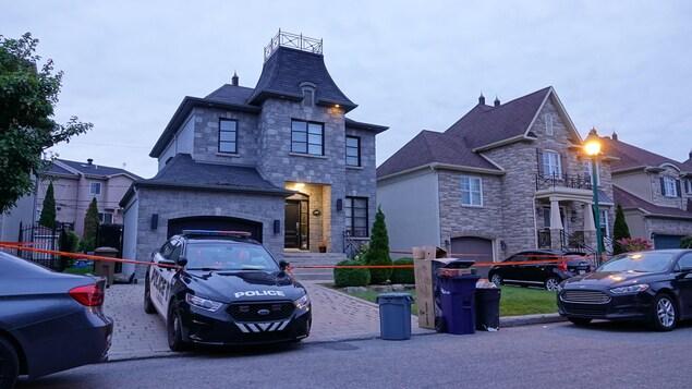 Une voiture de police devant une maison à Laval