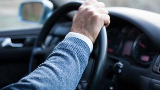 Une personne aînée qui conduit.