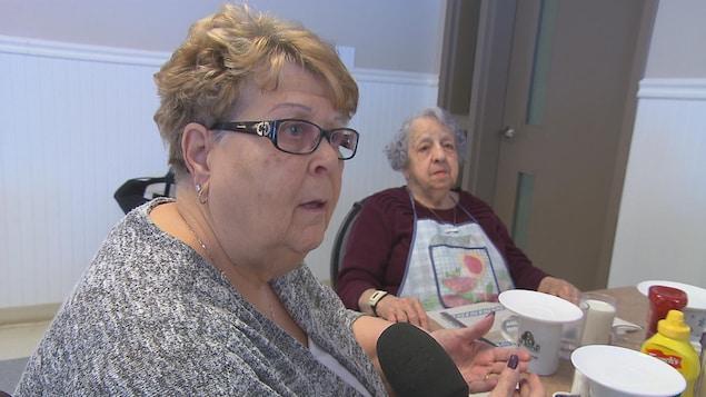 Hermine Hébert discute à table avec d'autres résidents.