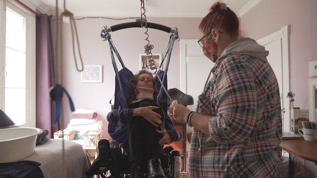 Nancy Leblond transfère Marie-Claude Lépine vers son lit au moyen d'un lève-personne.