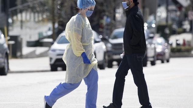 Un travailleur de la santé portant un équipement de protection individuelle complet traverse la rue devant l'hôpital Royal Columbian à New Westminster, en Colombie-Britannique.