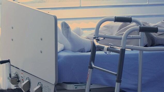 Une personne âgée étendue sur un lit de soins de longue durée à l'hôpital de Baie-Comeau.