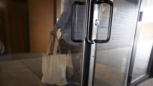 Une personne de dos, portant un sac à la main, derrière une porte de verre.