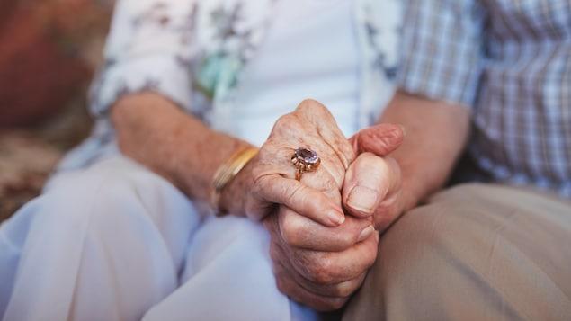 Gros plan sur les mains de personnes âgées.