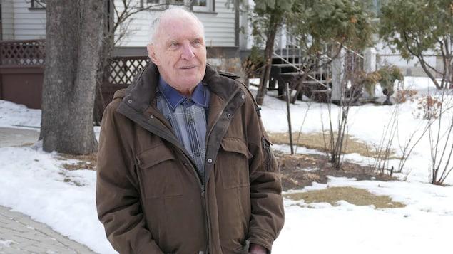 Peter Hanlon, les mains dans les poches de son manteau, dehors devant une maison.
