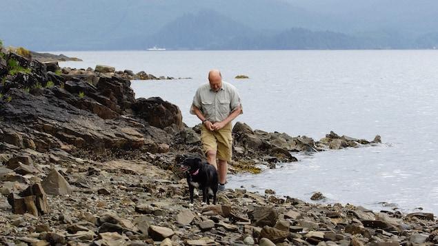 Peter Lake marche sur le bord de l'eau avec son chien noir.