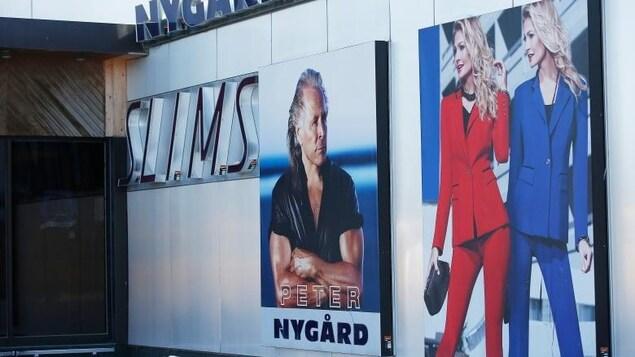 Une grande affiche murale sur laquelle on voit à gauche l'image d'un homme et à droite deux dames debout en tailleur.