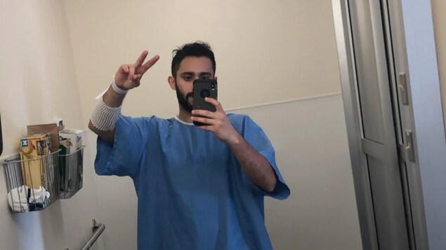 Peter Soliman prend un egoportrait devant le miroir du salle de bain d'hôpital, vêtu d'une chemise d'hôpital.
