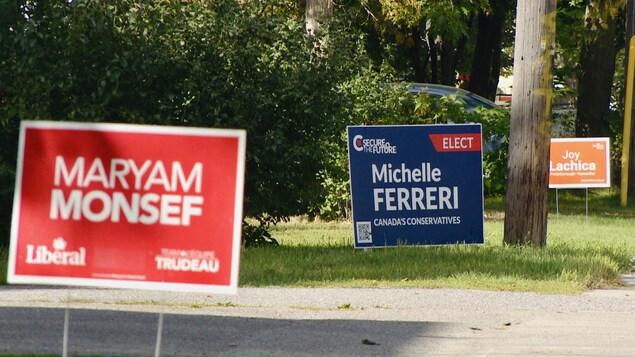 Trois affiches électorales dans une rue; une rouge, avec le nom de Maryam Monsef, une bleue, avec le nom de Michelle Ferreri, une orange avec le nom de Joy Lachica.