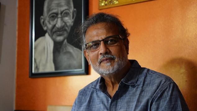 Un homme devant un cadre représentant le mahatma Gandhi.