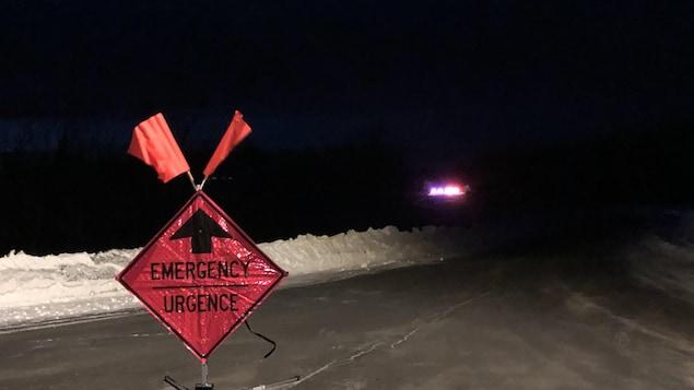 Un panneau sur lequel est écrit URGENCE au milieu d'une autoroute bloquée. Au loin, les gyrophares d'une voiture de police.