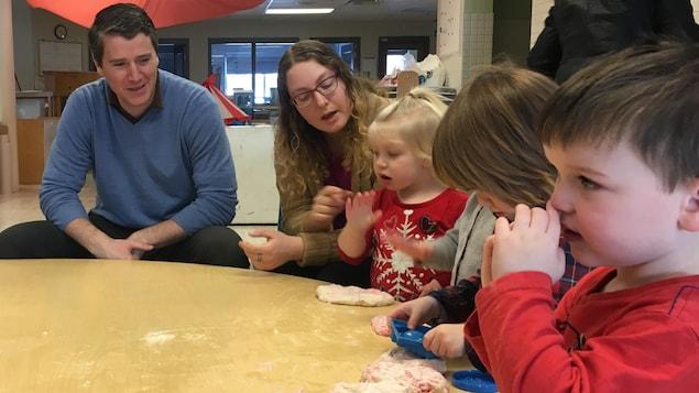 Un homme et une femme sont assis à une table de jeu avec des enfants qui s'amusent avec de la pâte à modeler.