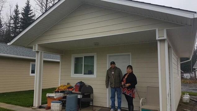 Un homme et une femme debout devant une petite maison