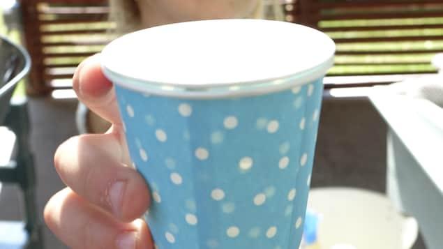 Une jeune fille tient une tasse.