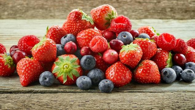 Des petits fruits reposent sur une table.
