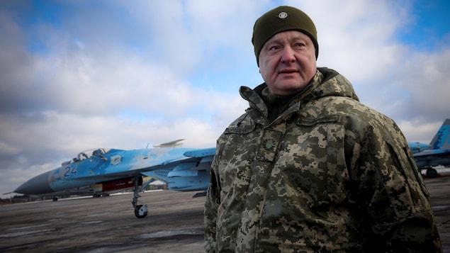 Petro Porochenko pose en habit de camouflage sur un tarmac, un avion militaire se trouve derrière lui.
