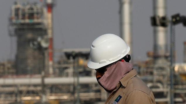 Un travailleur devant les installations d'un complexe pétrolier.