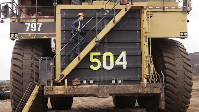 Un travailleur monte une échelle intégrée à l'avant du camion afin d'atteindre sa cabine située à 5 hauteurs d'homme.