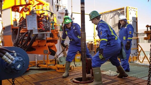 Trois employés du secteur pétrolier travaillent avec une machine de forage sur un navire.
