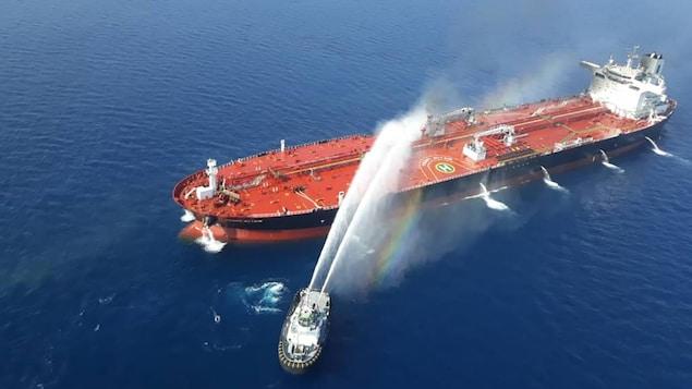 Des jets d'eau sont tirés d'un bateau-pompe en direction d'un pétrolier.