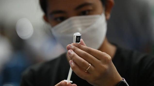 Un travailleur de la santé tient un vaccin contre la COVID-19.
