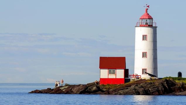 Un phare rouge et blanc sur une péninsule rocheuse du Québec.