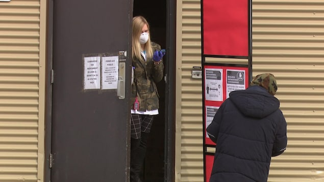 Une jeune femme qui porte un masque et des gants parle à un homme à travers une porte entrouverte