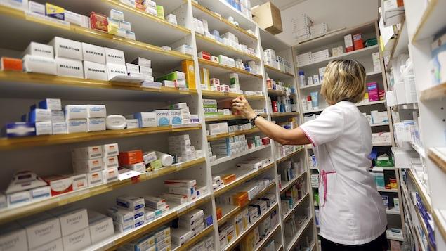 Une pharmacienne recherche un médicament parmi les nombreux produits placés sur des étagères de son magasin